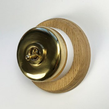 Round Dolly Light Switch on Circular Oak Base Polished Brass, on White Mount