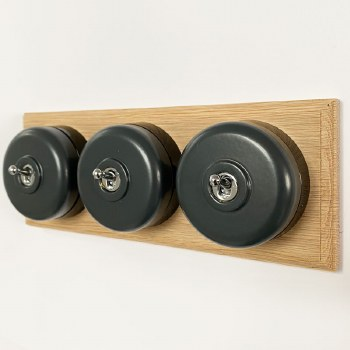 Round Dolly Light Switch 3 Gang Dark Grey on Oak Pattress with Black Mount