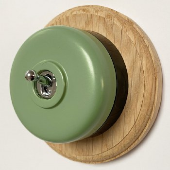 Round Dolly Light Switch Green on Circular Oak Base with Black Mount