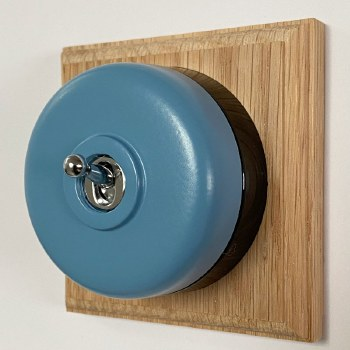Round Dolly Light Switch Blue on Square Oak Pattress with Black Mount