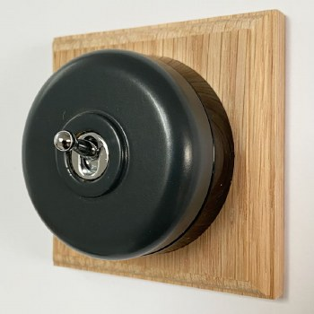 Round Dolly Light Switch Dark Grey on Square Oak Pattress with Black Mount
