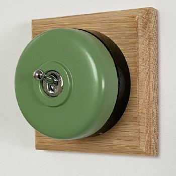 Round Dolly Light Switch Green on Square Oak Pattress with Black Mount