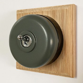 Round Dolly Light Switch Light Grey on Square Oak Pattress with Black Mount