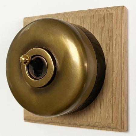 Round Dolly Light Switch on Oak Base Antique Satin Brass 1 Gang