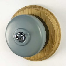 Round Dolly Light Switch Light Grey on Circular Oak Base with Black Mount