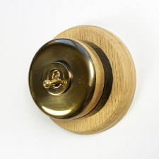 Round Dolly Light Switch on Circular Oak Base Polished Brass on Black Mount