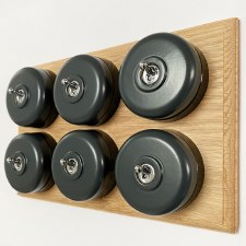 Round Dolly Light Switch 6 Gang Dark Grey on Oak Pattress with Black Mounts