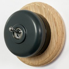 Round Dolly Light Switch Dark Grey on Circular Oak Base with Black Mount