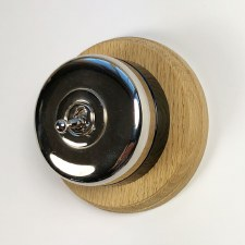 Round Dolly Light Switch on Circular Oak Base Nickel, on Black Mount