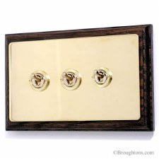 Victorian Dolly Switch on Wooden Pattress 3 Gang Polished Brass