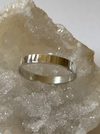 Band with a hammered texture that looks like lines. Handmade in Sterling Silver