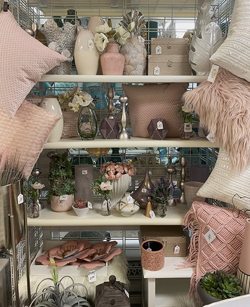 shelves of pink glass vases and decorations